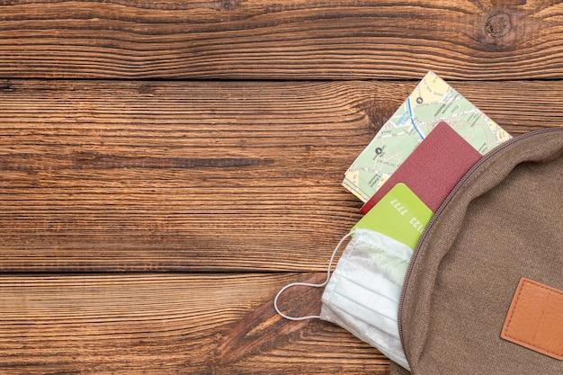 観光マップ、クレジットカード、パスポート、コピースペースのある木製の背景に旅行のバックパックから突き出た保護マスク