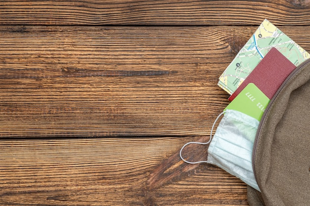 Туристическая карта, кредитная карта, паспорт, защитная маска из дорожного рюкзака на деревянном