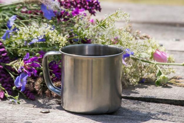 花の横にあるツーリストメタルカップは灰色の木製テーブルの上に立っています