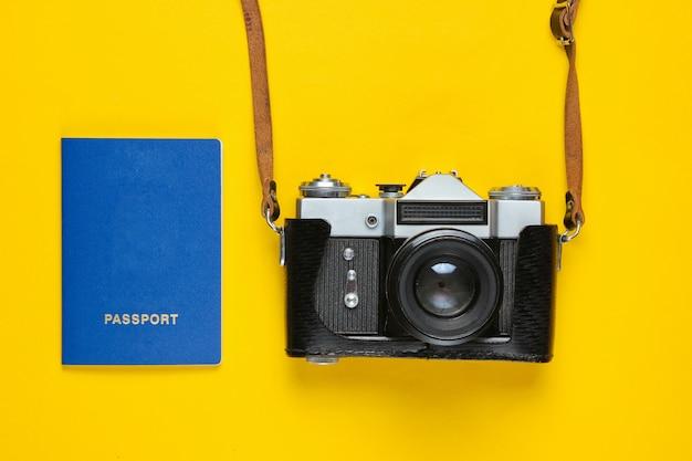 Концепция туристического минимализма. плоские лежал путешествия, концепция поездки. ретро фотоаппарат и паспорт на желтом.