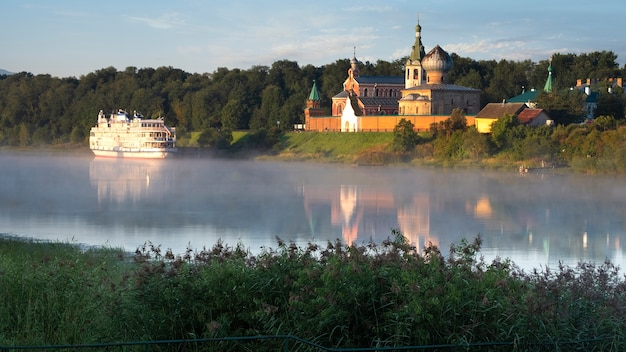 A tourist motor ship against the background of the male nikolsky monastery in staraya ladoga in the leningrad region on a foggy morning on the volkhov river. traveling on the rivers of russia