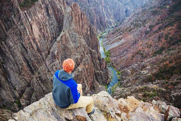 Турист на гранитных скалах черного каньона ганнисона, колорадо, сша