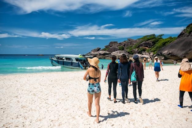 Туристы идут по белому песчаному пляжу острова ко-симилан № 8 на скоростной лодке после посещения летнего ориентира на скале в пханг нга, таиланд.