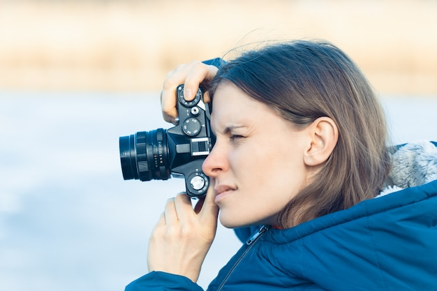 A tourist photographer takes pictures with a vintage retro film camera - a woman takes pictures at a photography lesson.