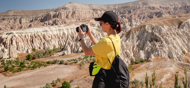 Tourist photographing unusual panoramic landscape with mountains in cappadocia, turkey