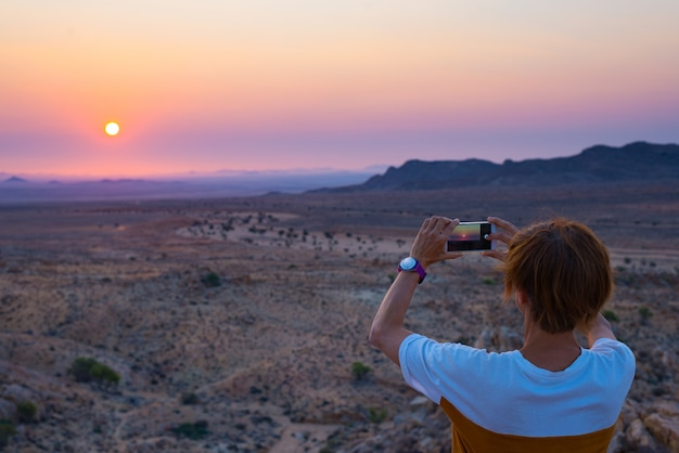 Tourist photographing with smartphone the stunning view of barren valley in the namib desert