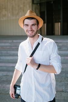 観光写真。旅行者は彼の冒険を思い出すためにたくさんの写真を撮ります。笑顔の若い男。