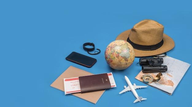 Турист планирует отдых с помощью карты мира с другими туристическими принадлежностями. смартфон, пленочная камера и солнцезащитные очки на синей стене.