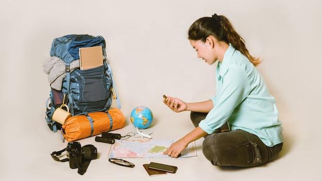 Турист планирует отдых с помощью карты мира с другими туристическими принадлежностями.