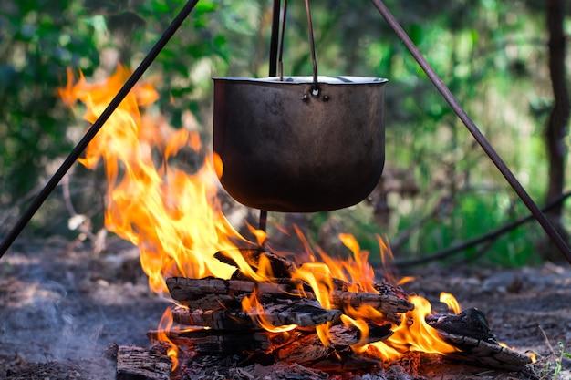 Туристический горшок, висящий над огнем на треноге. готовим в походе.