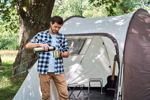 キャンプテント近くの魔法瓶からお茶を注ぐ観光客
