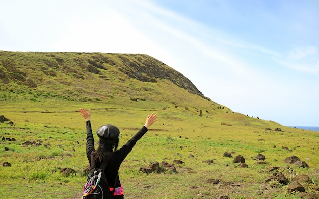 Tourist raising arms excited to visit rano raraku volcano, quarry of the famous moai statue on easter island
