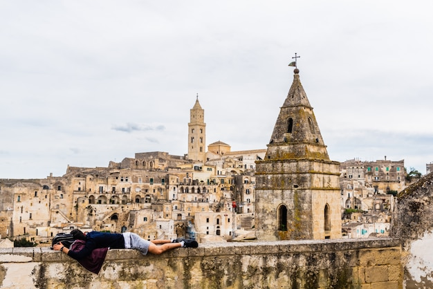 Tourist resting lying on a square in the city of matera, in italy.