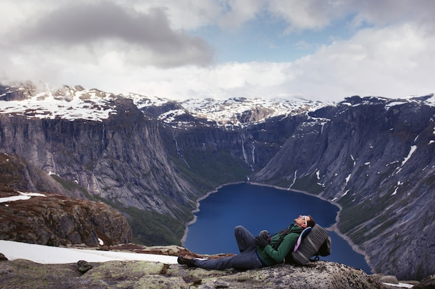 Tourist rests before beautiful view on mountain lake somewhere in norway