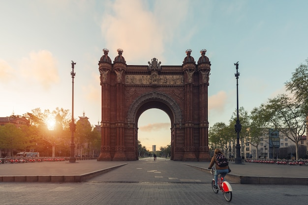 Tourist riding bicycle near bacelona arc de triomf during sunrise in barcelona in catalonia, spain.