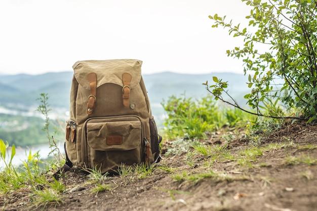 崖の端にある観光客の茶色のバックパック