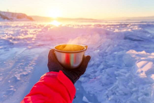 Tourist`s hand holding a steaming mug in winter landscape outdoors. winter and rourism concept