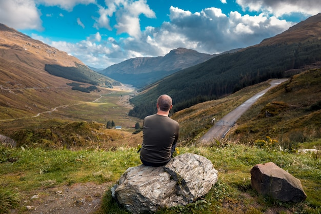 Tourist in scotland sits with his back to the camera