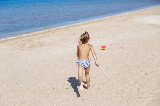 관광 시즌: 아이가 해변을 산책합니다. 바다로 휴가