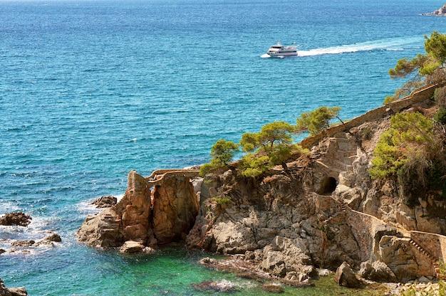 青い海と古い岩の上の観光船の定期船