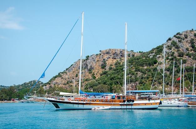 地中海の美しい夏の山の風景の背景に観光船。