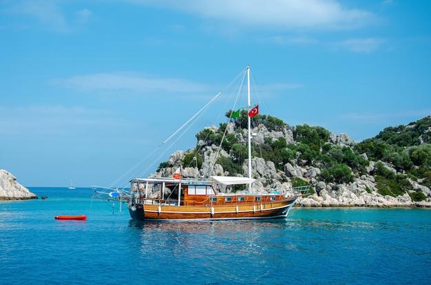 Туристический корабль на фоне красивого летнего горного пейзажа на средиземном море.
