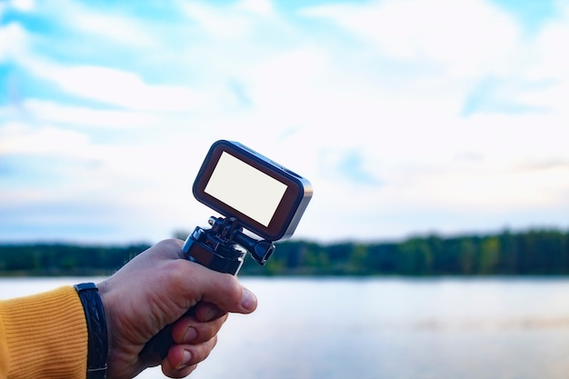 Tourist shoots a video on an action camera in nature
