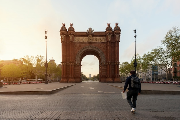 Tourist sightseeing bacelona arc de triomf during sunrise in barcelona in catalonia, spain