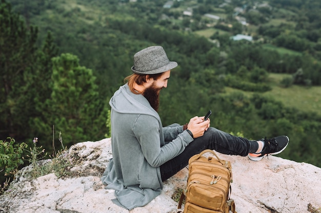 Tourist sit on a high rock with a phone in his hand.