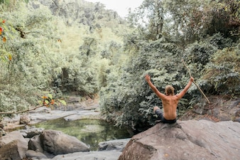 Tourist sits on a stone in the forest. Sumbawa