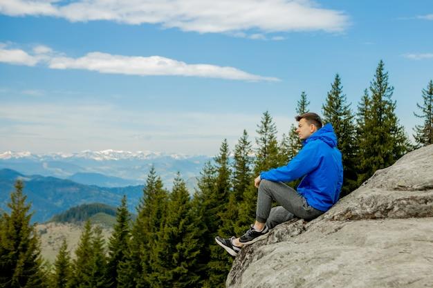 観光客は崖の上に座って、遠くを見ています。男が座る。素晴らしい山の風景。夏は時間です