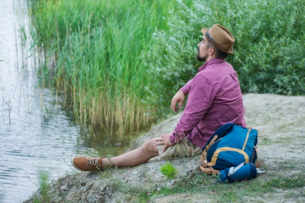 관광객은 여행용 배낭을 메고 호수 기슭에 앉는다.