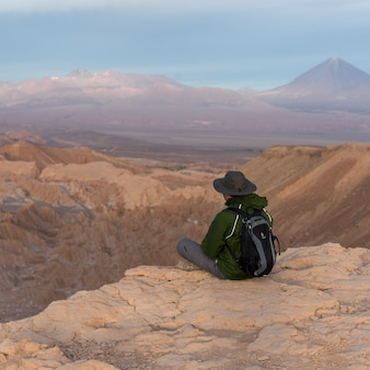 Tourist sitting on edge of cliff, death valley, san pedro de atacama, el loa province, antofagasta r