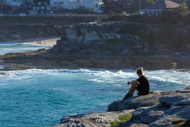 Tourist sitting on the edge of rock cliff looking to the blue ocean