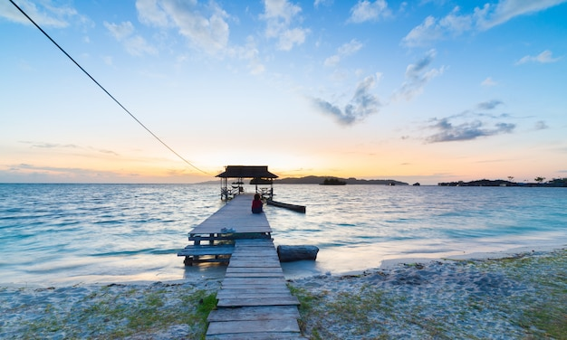 Tourist sitting on wooden jetty at sunrise, indonesia
