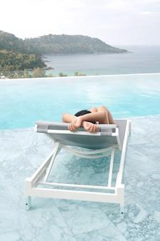 Tourist sleep on deckchair and swimming pool