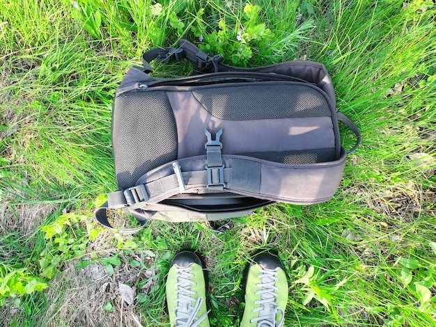 Tourist sneakers and backpack on green grass