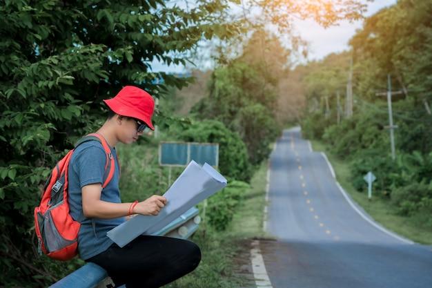 Турист стоит и смотрит на карту на дороге, долгий путь.