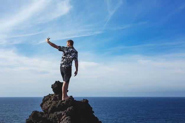 배경 푸른 바다에 바위에 서서 그의 스마트 폰 카메라로 사진을 찍는 관광객. 스페인 란사로테 섬.