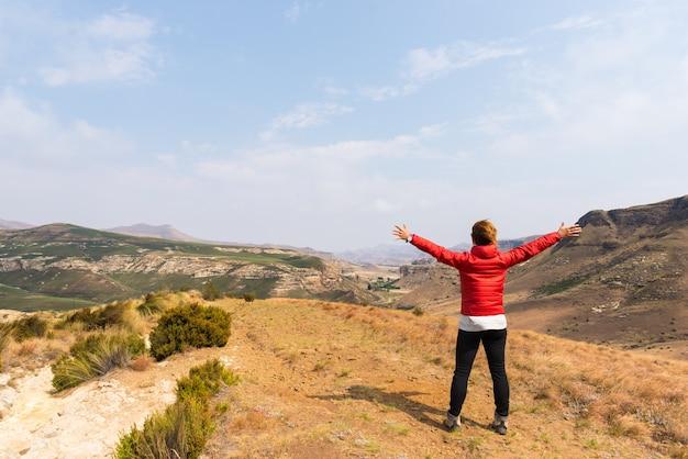 Турист стоит с распростертыми объятиями и смотрит на панорамный вид