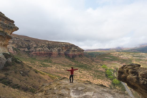 Tourist standing with outstretched arms and looking at the panoramic view in the majestic golden gate highlands national park, travel destination in south africa. adventure and traveling people.