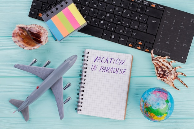 Tourist stuff with notebook, toy airplane, seashell, globe on blue background. flat lay from above.