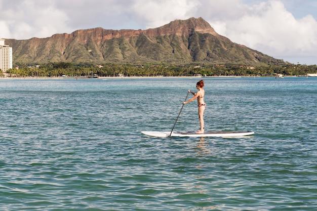 ダイヤモンドヘッド山を背景にサーフィンをする観光客