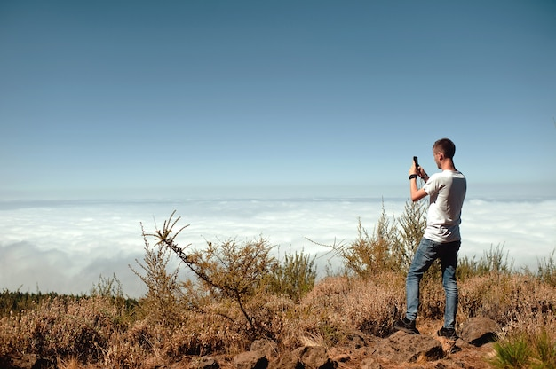 Tourist taking photo of beautiful mountain landscape with mobile phone