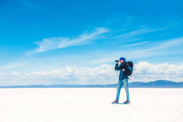 Tourist taking photo in sunshine salar de uyuni