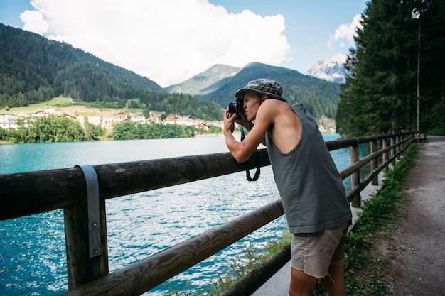 Tourist taking photos of nature landscape using his smartphone