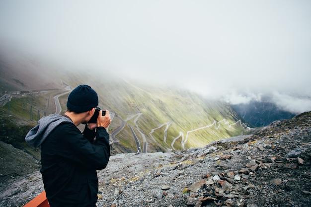 彼のスマートフォンを使用して自然の風景の写真を撮る観光客