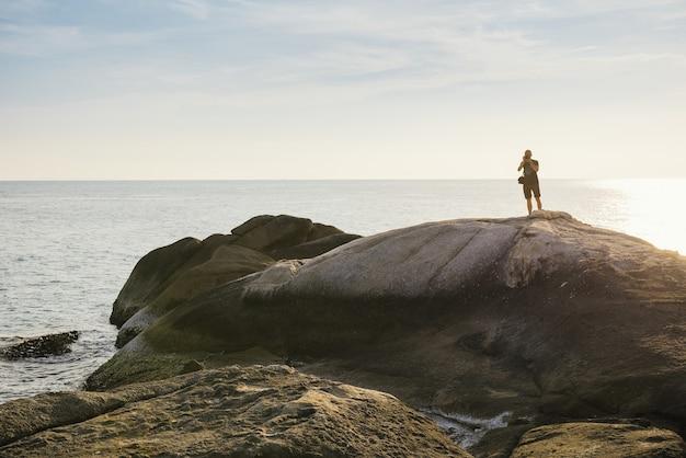 Турист, фотографирующий на вершине скалы у моря в таиланде. чистая и спокойная сцена заката на острове ко панган. исследование природы
