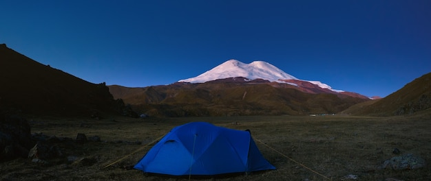 Tourist tent on the background of the snowy peaks of mount elbrus in russia. photographed in the early morning.