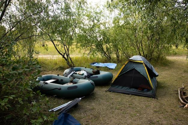 Туристическая палатка, надувные лодки в лесном лагере среди деревьев.
